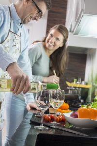 Man pouring white wine in glasses while cooking with woman at kitchen