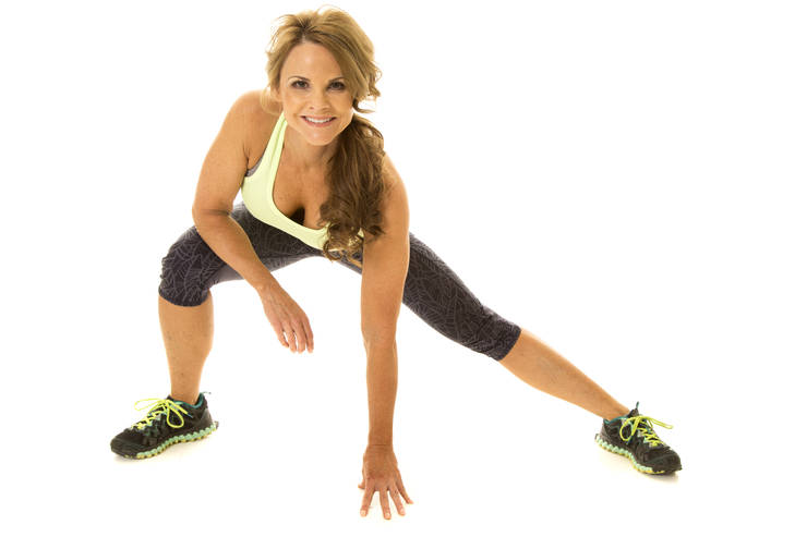 An older woman with a smile on her face, stretching out her body.